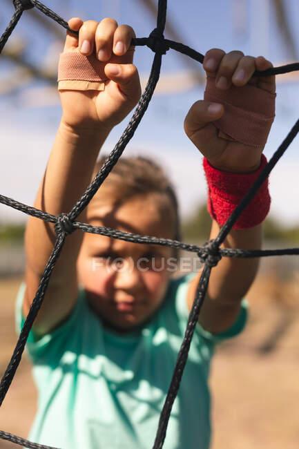 Primer plano de la chica caucásica en un campamento de arranque en un día soleado, subiendo por una red en un marco de escalada con yesos pegados en su mano, con una sudadera roja, camiseta verde y pantalones cortos negros, retroiluminado - foto de stock