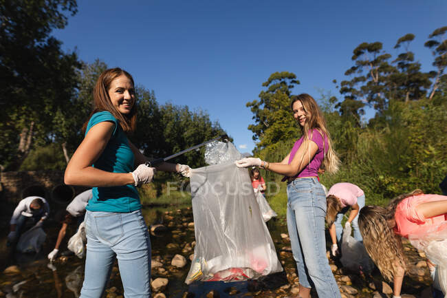 Portrait of two Caucasian female conservation volunteers cleaning up river in the countryside,  friends picking up rubbish in the background. Ecology and social responsibility in rural environment. — Stock Photo