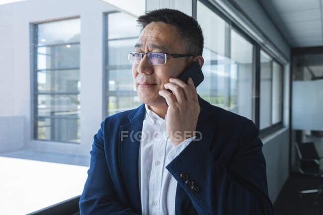 Inteligente casualmente vestido asiático masculino de negócios criativo vestindo óculos olhando para fora da janela sorrindo, falando no smartphone. Profissional de negócios criativos trabalhando em um escritório moderno. — Fotografia de Stock