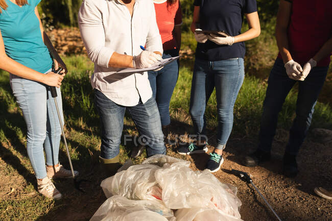 Low section of group of conservation volunteers cleaning up river in the countryside, bags of collected rubbish in front of them. Ecology and social responsibility in rural environment. — Stock Photo