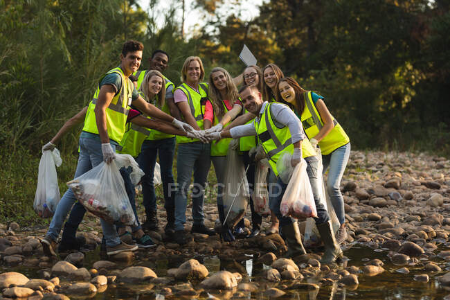 Multi-ethnic group of happy conservation volunteers cleaning up river in the countryside, holding rubbish bags, hand stacking. Ecology and social responsibility in a rural environment. — Stock Photo