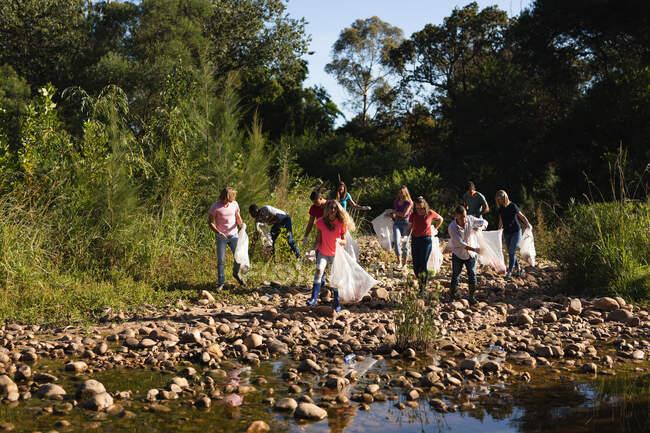 Un gruppo multietnico di volontari per la conservazione pulisce il fiume nelle campagne, raccogliendo spazzatura. Ecologia e responsabilità sociale nell'ambiente rurale. — Foto stock