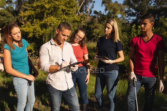 Multi ethnic group of conservation volunteers cleaning up river in the countryside, man making notes holding clipboard. Ecology and social responsibility in rural environment. — Stock Photo