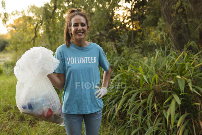 Portrait of happy Caucasian female conservation volunteer cleaning up forest in the countryside, holding rubbish bag, smiling to camera. Ecology and social responsibility in rural environment. — Stock Photo