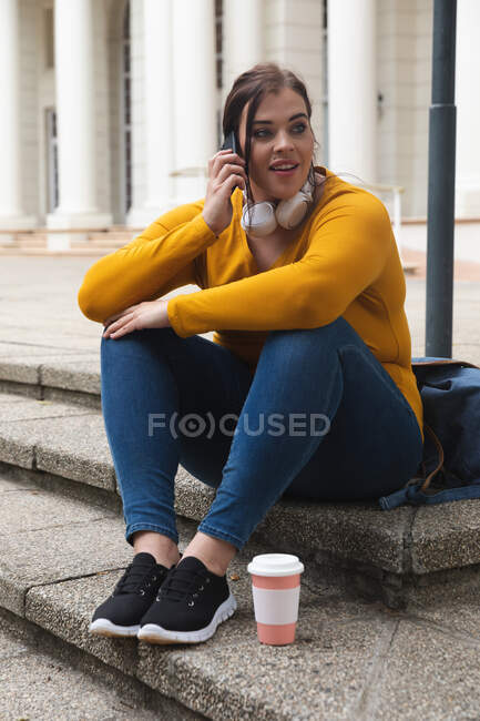 Curvy Caucasian woman out and about in the city streets during the day, sitting on steps with a takeaway coffee, talking on smartphone, wearing headphones, with a historical building in the background — Stock Photo