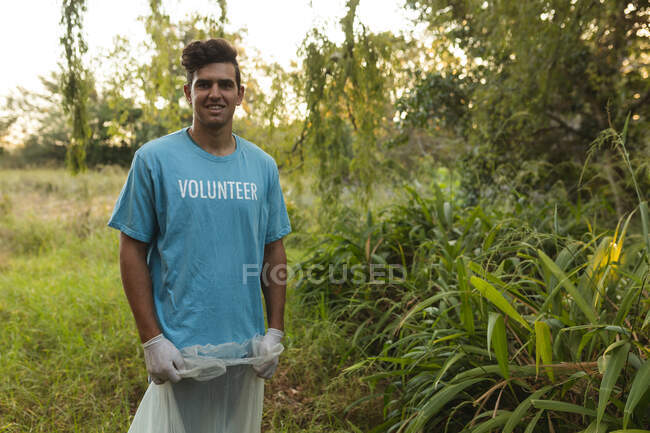 Portrait of happy mixed race male conservation volunteer cleaning up forest in the countryside, holding rubbish bag, smiling to camera. Ecology and social responsibility in rural environment. — Stock Photo