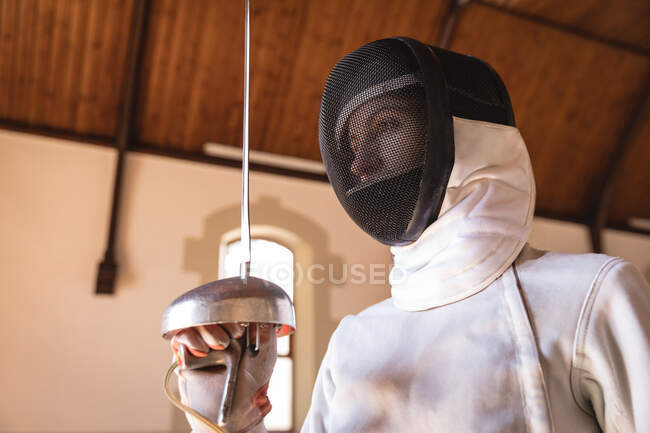 Caucasian sportswoman wearing protective fencing outfit during a fencing training session, preparing for a duel, holding an epee. Fencers training at a gym. — Stock Photo