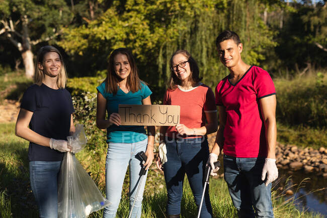 Portrait de plusieurs groupes ethniques de bénévoles heureux pour la conservation nettoyant la rivière à la campagne avec planche Merci. Écologie et responsabilité sociale en milieu rural. — Photo de stock