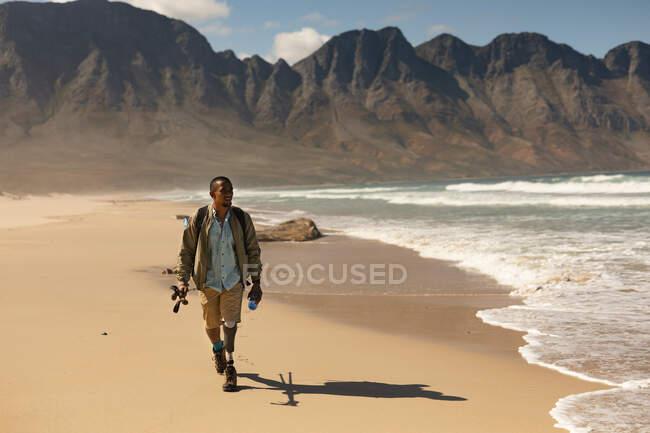 Un atleta maschio di razza mista in forma e disabile con gamba protesica, che si gode il suo tempo in gita in montagna, escursioni con bastoni, passeggiate sulla spiaggia in riva al mare. Stile di vita attivo con disabilità. — Foto stock