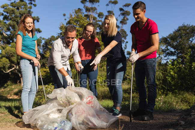 Multi ethnic group of conservation volunteers cleaning up river in the countryside, pointing at bags of collected rubbish in front. Ecology and social responsibility in rural environment. — Stock Photo