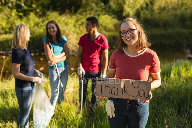 Portrait of of happy Caucasian female conservation volunteer cleaning up the countryside with board Thank You, her friends in the background. Ecology and social responsibility in rural environment. — Stock Photo