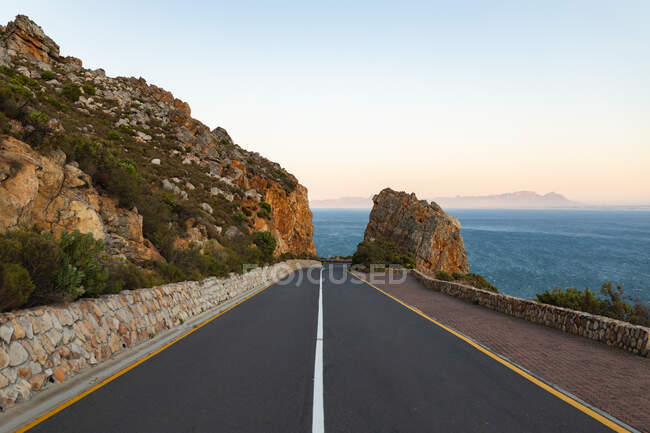 View showing an empty coastal asphalt road disappearing into the distance at the center of the image, cutting through mountains by the sea with a clear sky at sunset. — Stock Photo