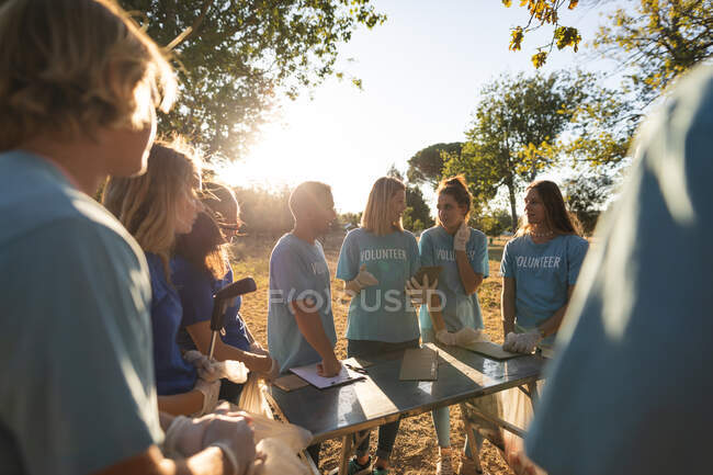 Multi ethnic group of conservation volunteers cleaning up forest in the countryside, talking around table. Ecology and social responsibility in rural environment. — Stock Photo