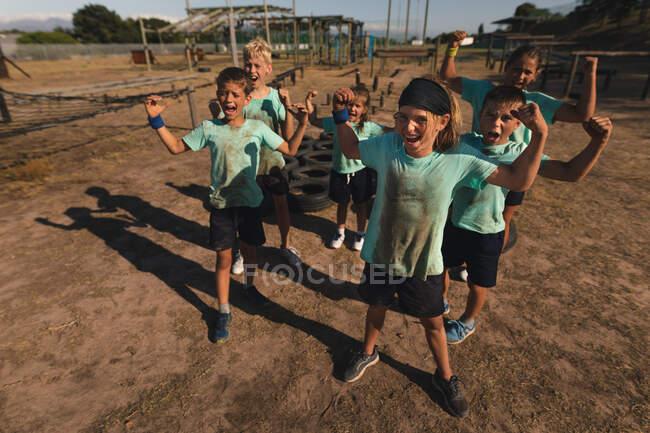 Un groupe de garçons et de filles caucasiens dans un camp de démarrage par une journée ensoleillée, portant des t-shirts verts sales et avec de la boue sur le visage, criant et fléchissant leurs biceps — Photo de stock