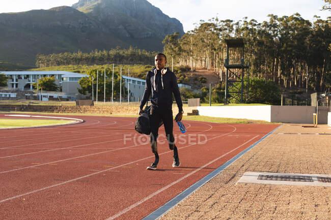 Atleta maschio disabile di razza mista in forma in uno stadio sportivo all'aperto, cammina con borsa da palestra e borraccia in pista indossando lame da corsa. Disabilità atletica allenamento sportivo. — Foto stock