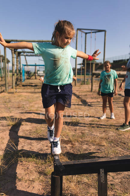 Caucasian girl at a boot camp on a sunny day, wearing green t shirt and black shorts, balancing and walking along a beam on an obstacle course with arms outstretched, with kids in the background — Stock Photo
