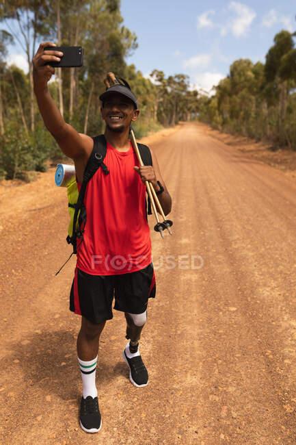 Fit, athlète masculin handicapé de race mixte avec jambe prothétique, profiter de son temps sur un voyage, randonnée, debout sur un chemin de terre dans une forêt, prendre des photos avec un smartphone. Mode de vie actif avec handicap. — Photo de stock