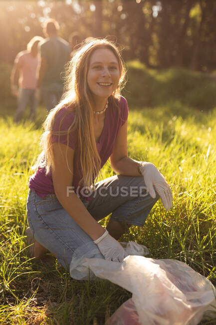 Portrait of happy female Caucasian female conservation volunteer with rubbish bag cleaning up forest in the countryside, smiling to camera. Ecology and social responsibility in rural environment. — Stock Photo