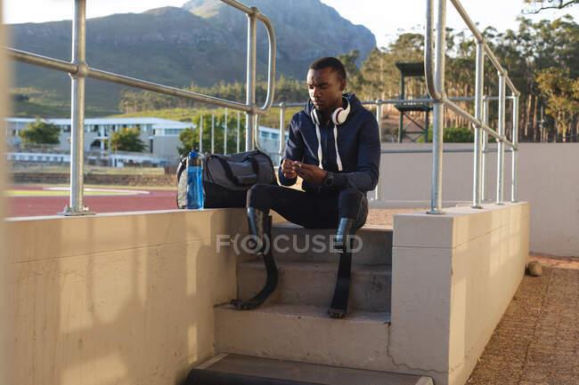 Atleta maschio disabile di razza mista in forma in uno stadio sportivo all'aperto, seduto con borsa da palestra e borraccia da corsa con lame da corsa. Disabilità atletica allenamento sportivo. — Foto stock
