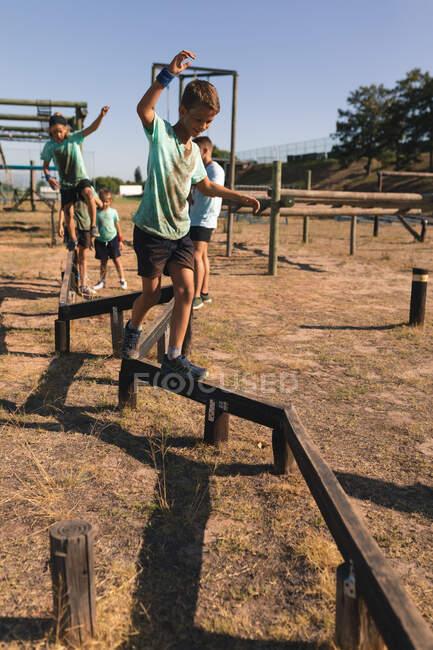 Garçon caucasien à un camp de démarrage par une journée ensoleillée, portant un t-shirt vert et un short noir, équilibrant et marchant le long d'une poutre sur un parcours d'obstacles, avec d'autres enfants le suivant en arrière-plan — Photo de stock