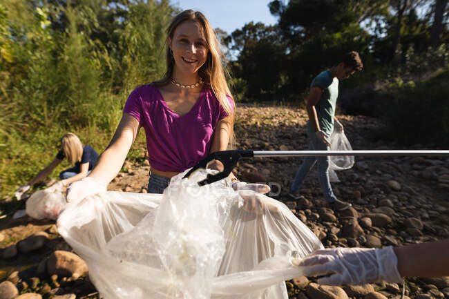 Portrait of Caucasian female conservation volunteer cleaning up river in the countryside, her friends picking up rubbish in the background. Ecology and social responsibility in rural environment. — Stock Photo