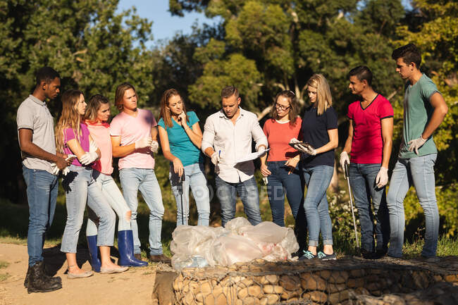 Multi ethnic group of conservation volunteers cleaning up river in the countryside, bags of collected rubbish in front of them. Ecology and social responsibility in rural environment. — Stock Photo