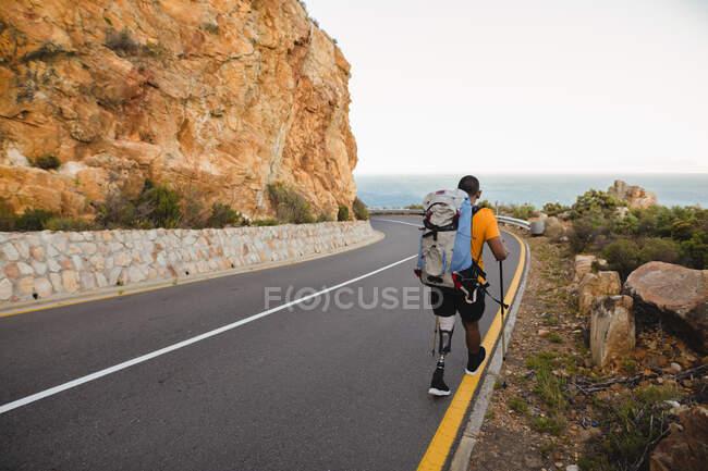 Подтянутый, инвалид смешанной расы спортсмен с протезной ногой, наслаждающийся путешествием в горы, походами с палками, прогулками по дороге у моря. Активный образ жизни с ограниченными возможностями. — стоковое фото