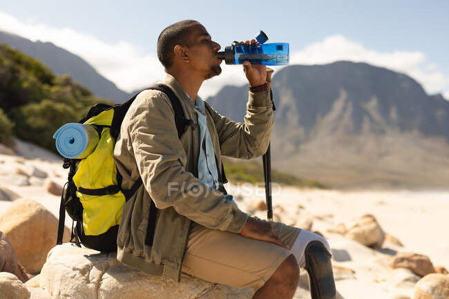 A fit, disabled mixed race male athlete with prosthetic leg, enjoying his time on a trip to the mountains, hiking with sticks, drinking water on the beach, resting. Active lifestyle with disability. — стоковое фото