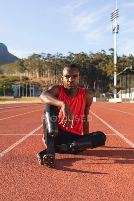 Портрет спортивного спортсмена-инвалида смешанной расы на открытом спортивном стадионе, сидящего на беговой дорожке с беговыми лезвиями. Спортивная подготовка для инвалидов. — стоковое фото
