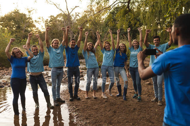Man taking photos of happy multi ethnic group of conservation volunteers cleaning up river in the countryside, smiling with arms in the air. Ecology and social responsibility in rural environment. — Stock Photo