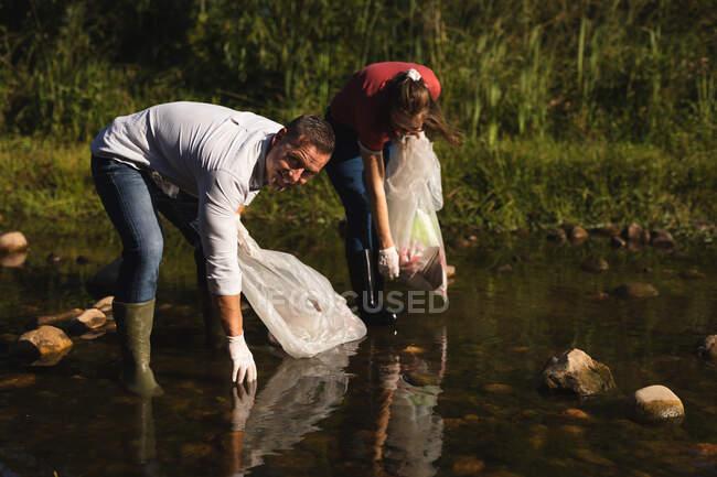 Портрет кавказского волонтера, очищающего реку в сельской местности, его подруги на заднем плане, собирающей мусор. Экология и социальная ответственность в сельской местности. — стоковое фото
