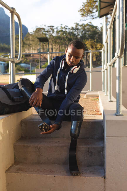 Fit, mixed race disabled male athlete at an outdoor sports stadium, preparing and sitting with gym bag by race track wearing running blades. Disability athletics sport training. — Stock Photo