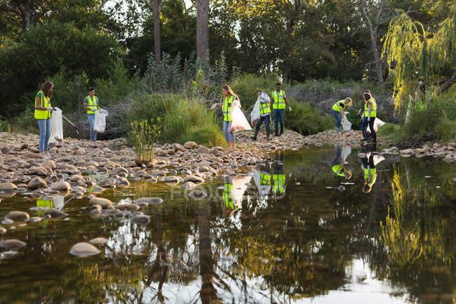 Grupo étnico multi de voluntários de conservação limpando o rio no campo, pegando lixo. Ecologia e responsabilidade social no meio rural. — Fotografia de Stock