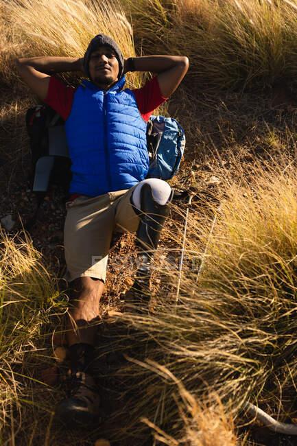 Atleta maschio di razza mista, in forma e disabile, con una gamba protesica, si gode il suo tempo in gita in montagna, riposandosi sull'erba. Stile di vita attivo con disabilità. — Foto stock