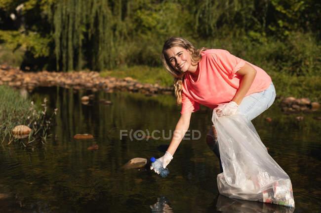 Портрет кавказьких жінок-добровольців для охорони природи очищають ріку в сільській місцевості, збираючи сміття. Екологія і соціальна відповідальність в сільському середовищі. — стокове фото