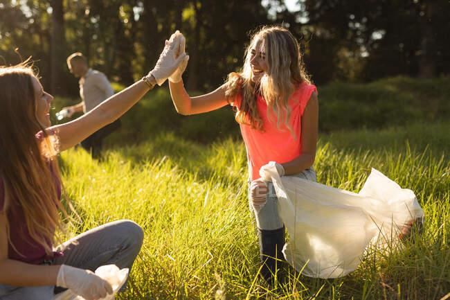 Две счастливые кавказские волонтёрки с мешками для мусора, убирающие лес в сельской местности, собирающие мусор