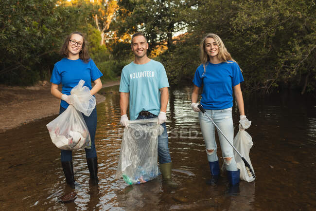 Three Caucasian male and female conservation volunteers cleaning up river in the countryside, holding rubbish bags and grabber. Ecology and social responsibility in rural environment. — Stock Photo