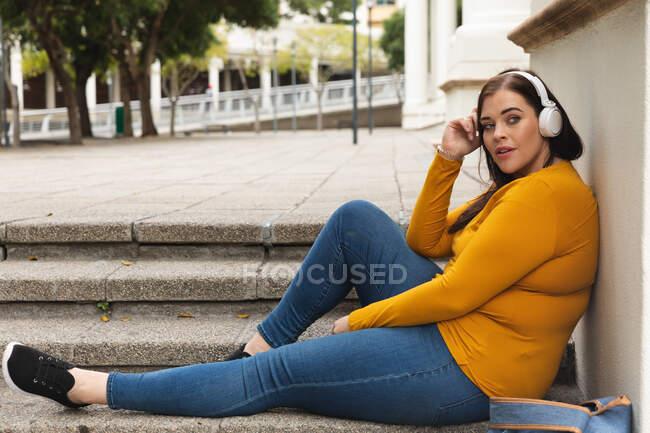 Mujer curvilínea caucásica por las calles de la ciudad durante el día, sentada en los escalones, inclinada hacia atrás y escuchando música en los auriculares, con edificio histórico en el fondo - foto de stock