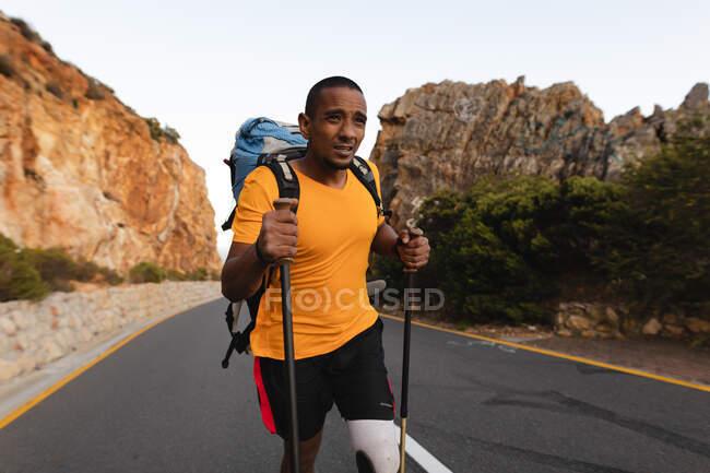 Athlète masculin de race mixte en forme et handicapé avec une jambe prothétique, profitant de son temps sur un voyage à la montagne, randonnée avec des bâtons, marche sur la route par la mer. Mode de vie actif avec handicap. — Photo de stock