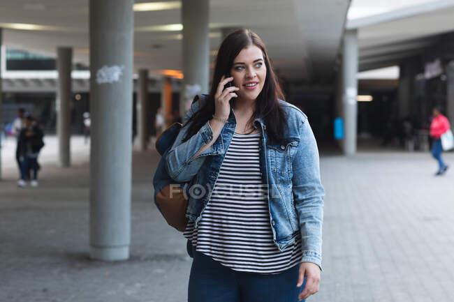 Curvy femme caucasienne dans les rues de la ville pendant la journée, souriant et utilisant son smartphone portant un sac à dos et marchant avec un bâtiment moderne en arrière-plan — Photo de stock