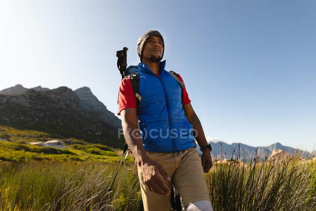 Придатний, інвалідний спортсмен змішаної раси з протезною ногою, насолоджуючись своїм часом у поїздці в гори, поході, поході по траві. Активний спосіб життя з інвалідністю. — стокове фото