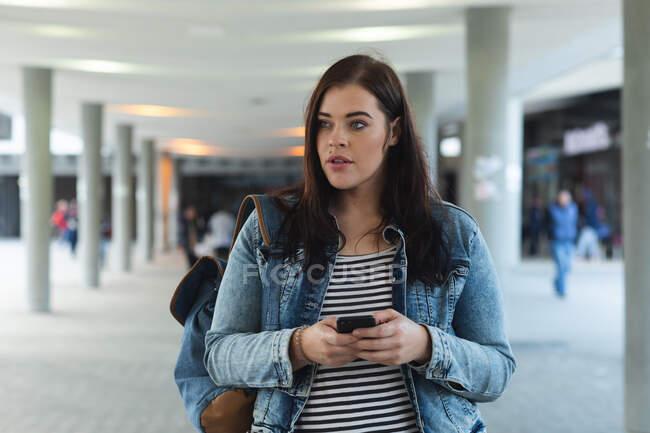 Игривая кавказка днем гуляет по улицам города, улыбаясь и пользуясь смартфоном, прогуливаясь с современным зданием на заднем плане — стоковое фото