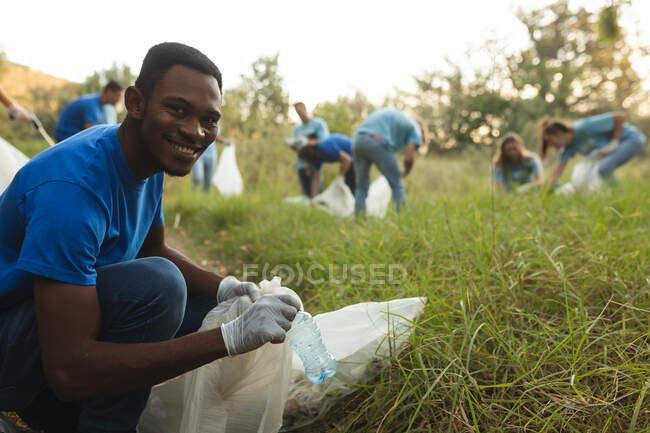 Retrato de afro-americanos voluntários de conservação do sexo masculino limpando a floresta no campo, sorrindo para câmera segurando saco de lixo. Ecologia e responsabilidade social no meio rural. — Fotografia de Stock