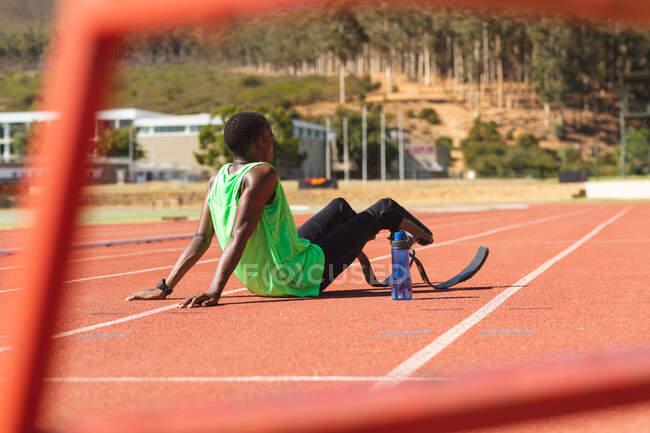 Спортивный спортсмен-инвалид смешанной расы на открытом спортивном стадионе, сидя на гоночной трассе за гонкой с бутылкой воды в беговых лопатках. Спортивная подготовка для инвалидов. — стоковое фото