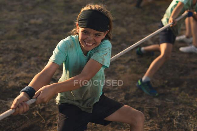 Ein kaukasisches Mädchen in schlammgrünem T-Shirt, schwarzer Hose und Haarband, das an einem sonnigen Tag bei einem Tauziehen in einem Bootcamp zusammen mit ihren Teamkollegen ein Seil zieht — Stockfoto