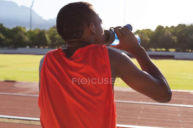 Передній вигляд придатного, змішаного чоловічого атлета на відкритому спортивному стадіоні, відпочиває і п'є з пляшки води на гоночній трасі. Тренування спортсменів. — стокове фото