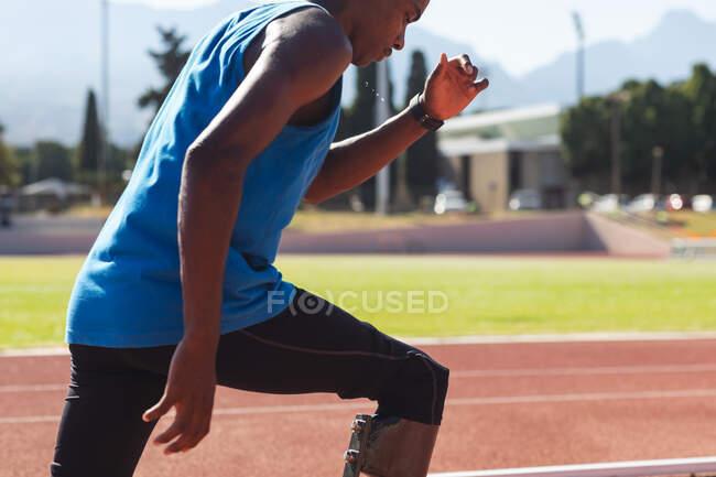 Средняя секция фитнеса, смешанный спортсмен мужского пола с протезными ногами на открытом спортивном стадионе, бегущий по беговой дорожке на беговых лопастях. Спортивная подготовка для инвалидов. — стоковое фото