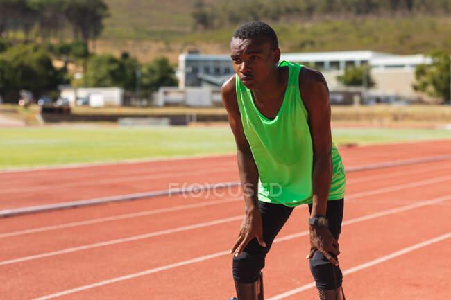 Спортивный спортсмен-инвалид смешанной расы на открытом спортивном стадионе, на гоночной трассе после гоночного дыхания и отдыха с беговыми ножами. Спортивная подготовка для инвалидов. — стоковое фото