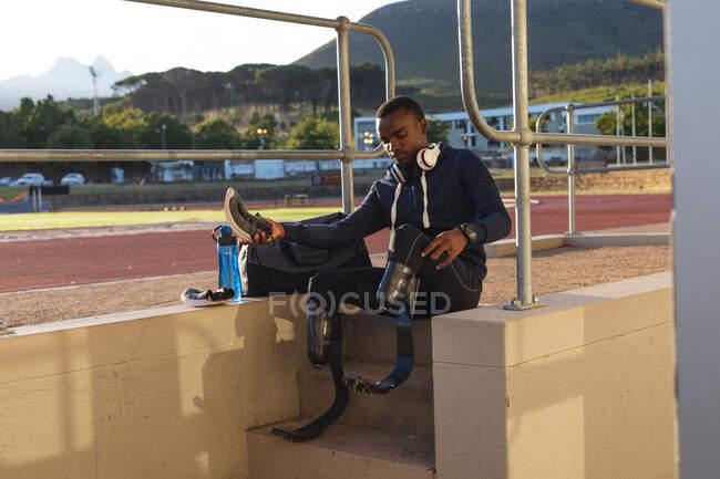 Atleta maschile disabile di razza mista in forma in uno stadio sportivo all'aperto, seduto in pista a preparare la tenuta di scarpe sportive con lame da corsa. Disabilità atletica allenamento sportivo. — Foto stock