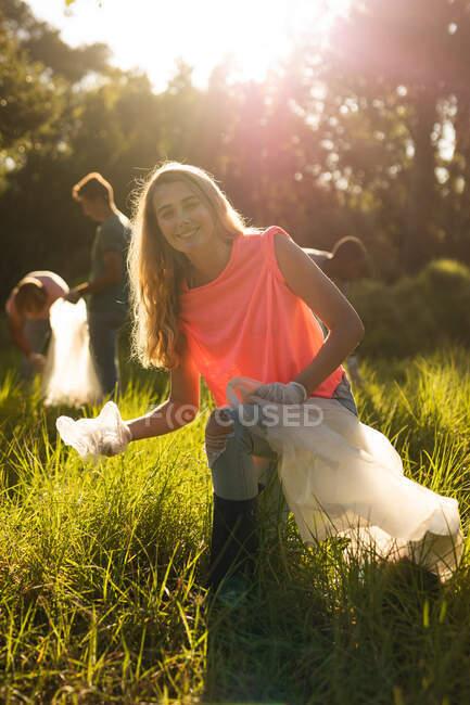 Портрет женщины-волонтера кавказской охраны природы с мусорными мешками, убирающей лес в сельской местности, улыбающейся в камеру. Экология и социальная ответственность в сельской местности. — стоковое фото